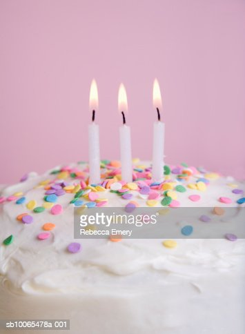 Birthday Cake With Sprinkles And Three Lit Candles Closeup Stock Photo