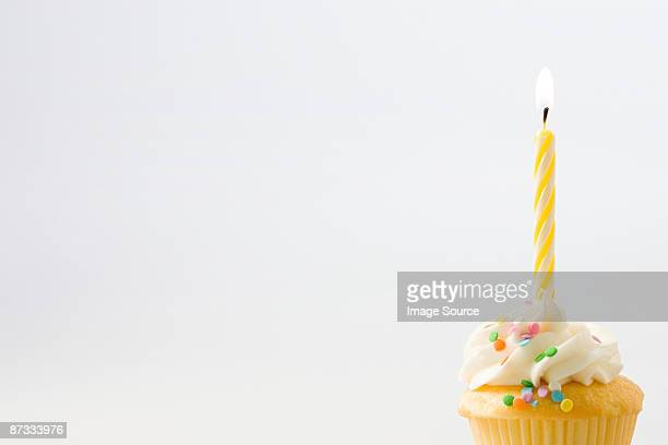 birthday candle on a cup cake - birthday cake stock photos and pictures