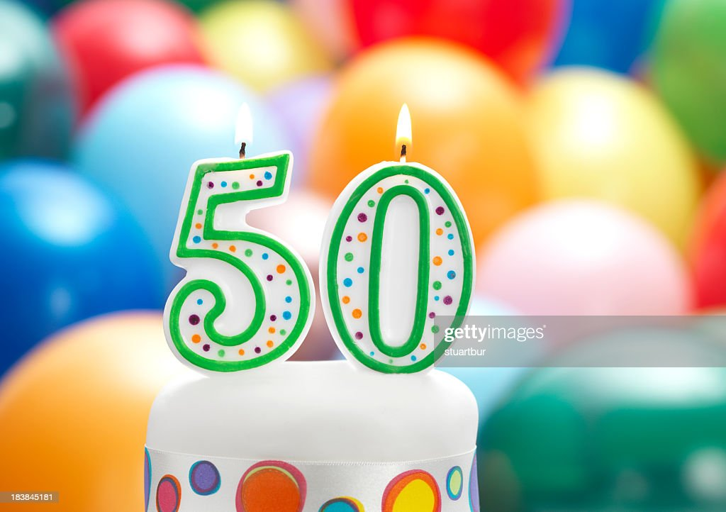 Birthday Candles That Say 50 With Blurred Balloons In Back Stock
