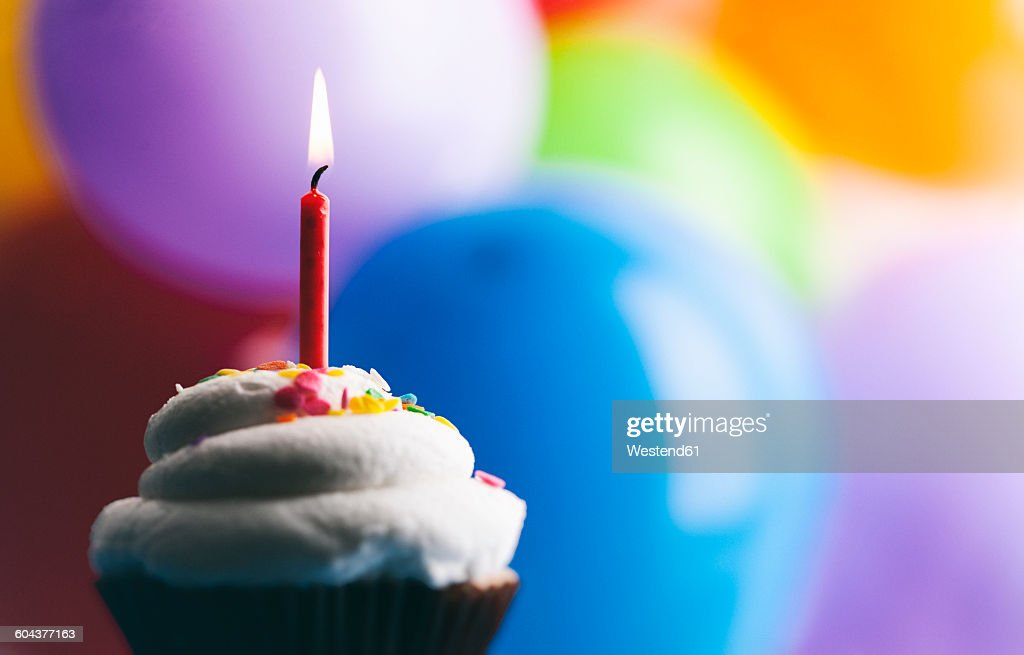 Birthday cup cake with lighted candle in front of balloons : Stock Photo