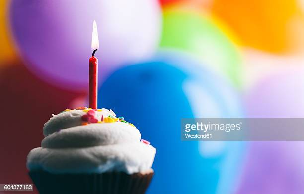 Birthday cup cake with lighted candle in front of balloons