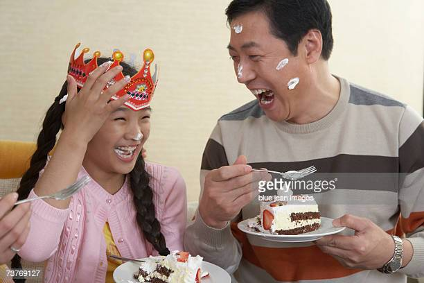 Birthday girl and her father have icing on their faces while they giddily eat the birthday cake.