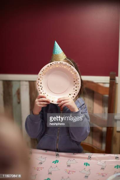 birthday girl covering face with plate - heshphoto stock pictures, royalty-free photos & images