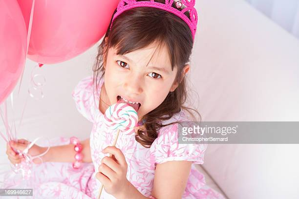 Birthday girl holding balloons and a lollipop
