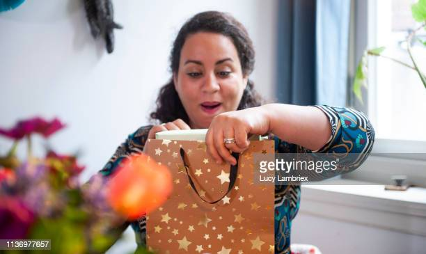 birthday girl is opening a gift bag with her present - birthday gift stock pictures, royalty-free photos & images