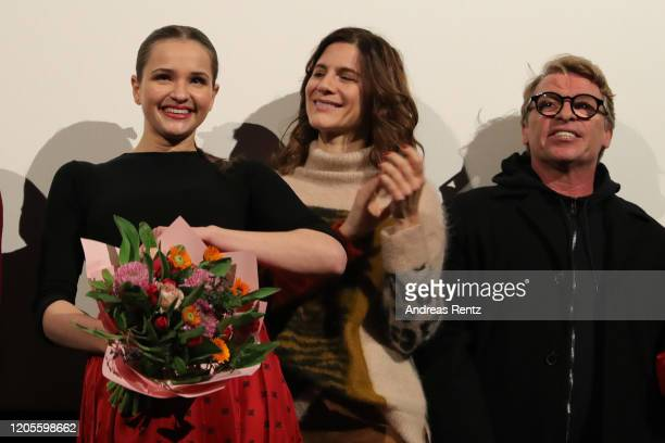 Birthday girl Lisa Vicari receives a bouquet of flowers while Christina Hecke and Andre Eisermann smile during the premiere of the Netflix film Isi...