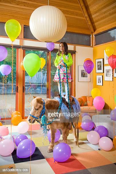 Birthday girl (6-7) standing on pony