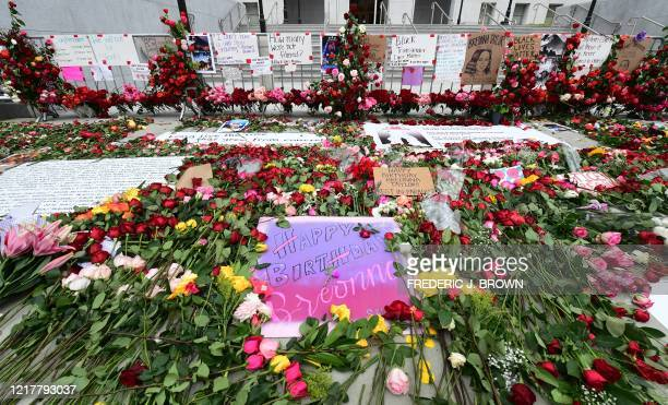 A birthday message for the late Breonna Taylor is surrounded by roses placed in a growing pile throughout the day in front of the Hall of Justice in...