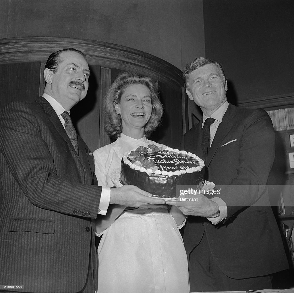 A large birthday cake, frosting and all, is delicately held by a threesome who have good reason to smile, producer David Merrick (left), actress Lauren Bacall, and actor Barry Nelson, Dec.7. Lauren and Nelson are starring in Merrick's Cactus Flower which is celebrating its first anniversary at the Royale Theater here.