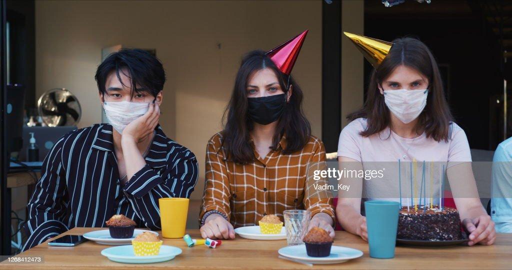 Geburtstagsparty von COVID-19 verwöhnt. Gleiten Sie entlang traurig verärgert multiethnische Freunde in Masken am Festtisch Zeitlupe. : Stock-Foto