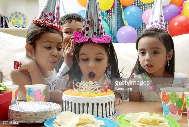 birthday party, young girl blowing candles on cake - fruit cake stock pictures, royalty-free photos & images