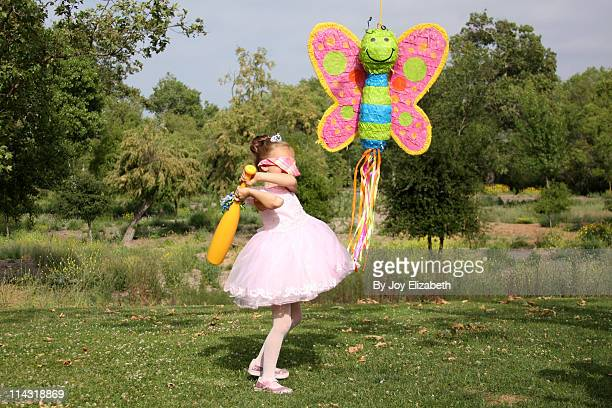 birthday princess girl swings at butterfly piñata - pinata stock pictures, royalty-free photos & images
