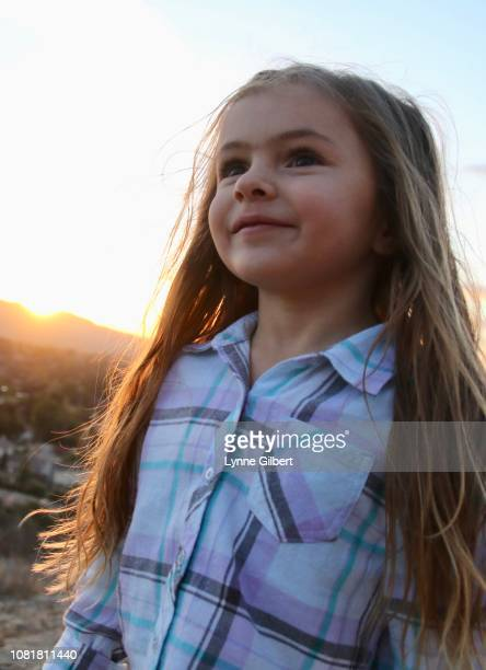 a birthday, sweet, little girl, with long hair, smiles during golden hour of sunset - golden hour stock pictures, royalty-free photos & images