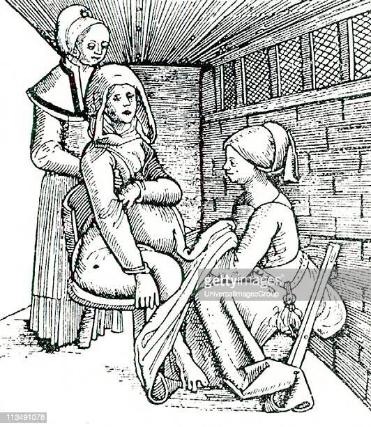 Birthing chair in use Midwife works underneath the mother's clothing while her assistant supports the mother from behind 16th century woodcut from...
