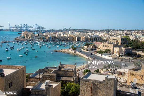 birzebbuga, malta: view of the town and the international port in the background - marsaxlokk stock pictures, royalty-free photos & images