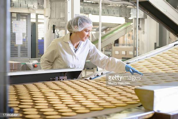 biscuit factory worker inspecting freshly made biscuits on production line - 飲食業 ストックフォトと画像