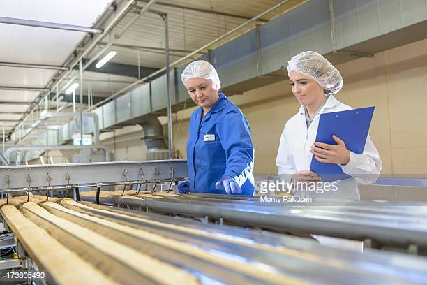 Biscuit factory workers inspecting freshly made biscuits on production line