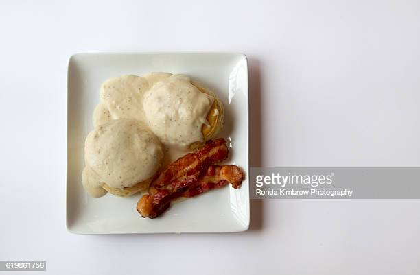 Biscuits and gravy with two slices of bacon isolated on white background