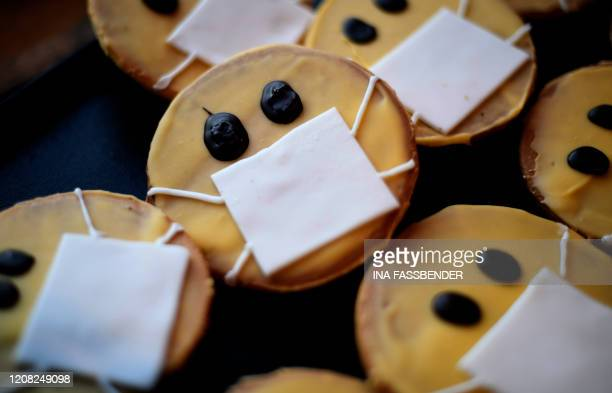 Biscuits featuring a face with a face mask are displayed at the bakery Schuerener Backparadies in Dortmund western Germany on March 26 2020 amidst...