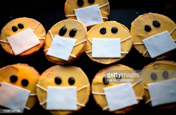 Biscuits featuring a face with a face mask are displayed at the bakery Schuerener Backparadies in Dortmund, western Germany, on March 26, 2020 amidst...