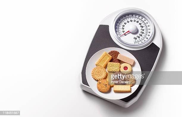 biscuits on bathroom scales with copy space - 不健康な食事 ストックフォトと画像