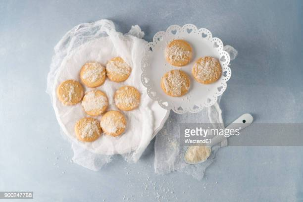 biscuits with sugar icing and coconut flakes - doily stock photos and pictures