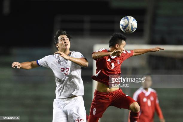 Bishal Rai of Nepal heads the ball with James Younghusband of the Philippines during the qualifying football match between the Philippines and Nepal...
