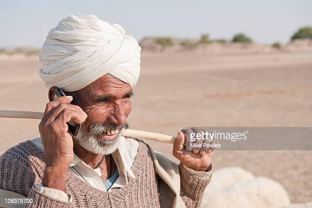 Bishnoi shepherd using mobile phone, Thar desert, Rajasthan, India