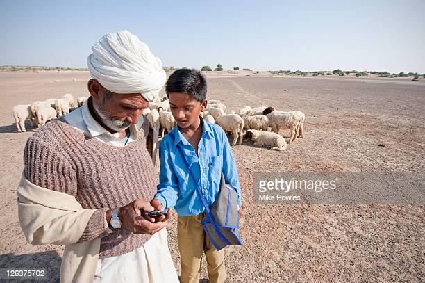 Bishnoi shepherd with boy, using mobile phone, Thar desert, Rajasthan, India