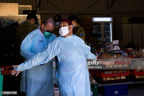 Bishop Columba helps Brendon Adams put on PPE before a food distribution to the community on September 06, 2021 in Wilcannia, Australia. After...
