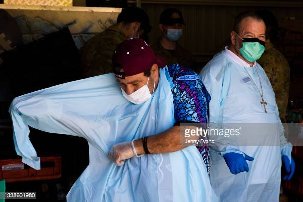 Bishop Columba laughs as Brendon Adams puts on PPE before a food distribution to the community on September 06, 2021 in Wilcannia, Australia. After...