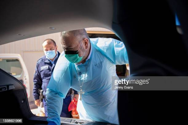 Bishop Columba packs items into a car ahead of a food distribution to the community on September 06, 2021 in Wilcannia, Australia. After hearing...