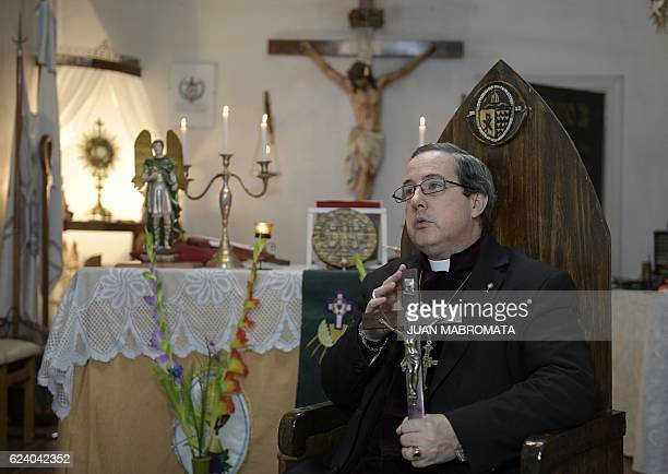 Bishop Manuel Acuna holds the crucifix he has used in many exorcisms as he speaks with AFP at the 'El Buen Pastor' parish in Santos Lugares outskirts...