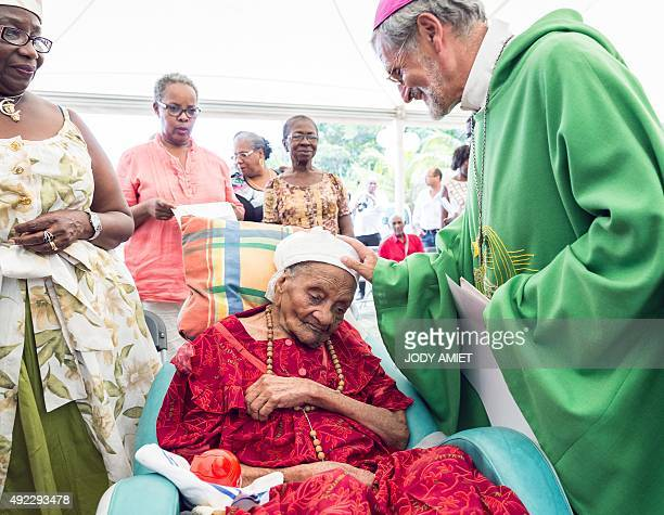 Bishop of Guiana Emmanuel Lafont touches the head of French supercentenarian and France's oldest living person in France Eudoxie Baboul 114 year...