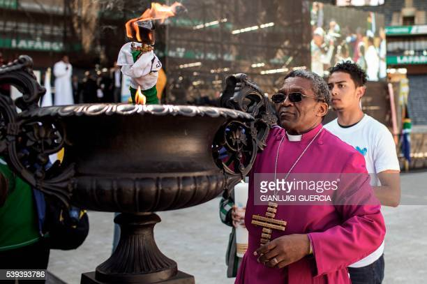 Bishop of the Ethiopian Episcopal Church South Africa's Malusi Mpumlwana holds a torch wrapped in the South African flag as he leads a peace walk in...
