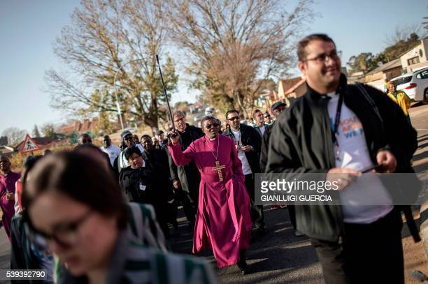 TOPSHOT Bishop of the Ethiopian Episcopal Church South Africa's Malusi Mpumlwana leads a peace walk in Soweto on June 11 2016 to commemorate the 40th...