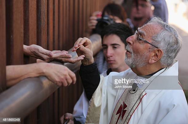 Bishop of Tucson Gerald Kicanas passes communion wafers through to the Mexican side of the USMexico border fence during a special 'Mass on the...