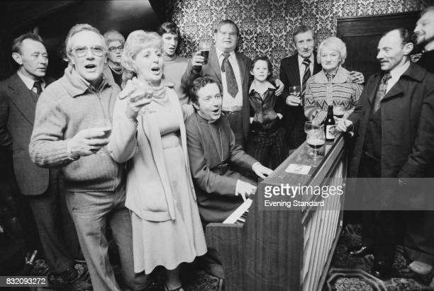 Bishop of Woolwich Michael Marshall plays the piano and sings along a group of people 13th March 1978