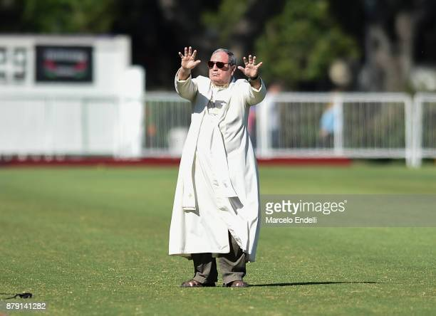 A bishop performs a prayer in honor to the 44 Argentine submarine crew members lost in the South Atlantic the during a match between La Dolfina and...