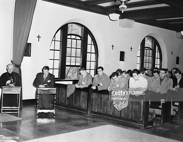 Bishop Raymond A Lane superior General of Maryknoll Seminary and Coach Frank Leahy kneel inside the altar rail in seminary chapel while members of...