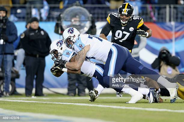 Bishop Sankey of the Tennessee Titans scores a touchdown as he is pushed by his teammate Taylor Lewan during the first quarter of the game against...