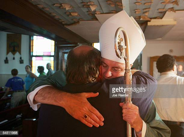 Bishop Thomas Rodi hugs city Mayor Eddie Favre as he enters to lead a mass at St Rose De Lima September 4 2005 in Bay St Louis Mississippi The town...