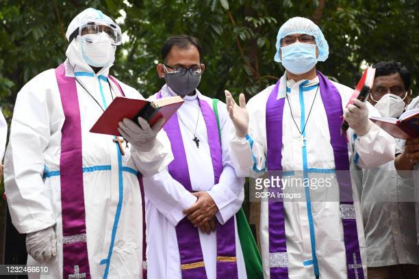 Bishop wearing a protective suite offering last prayers for a covid 19 deceased man during a burial by Bangladeshi Christians at a cemetery.