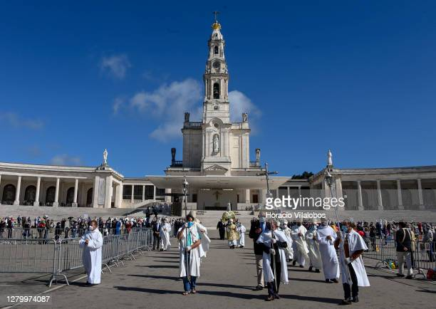 Bishops preceed masked bearers carrying the figure of Our Lady of Fátima back to the Chapel of Apparitions at the end of the ceremonies on the last...