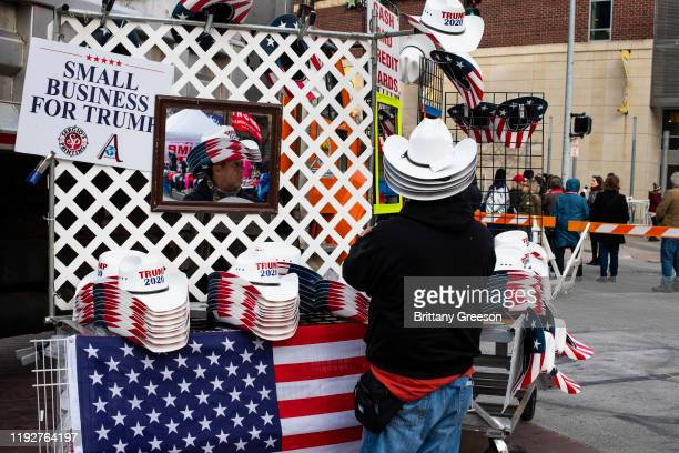 Biskit Godinez of Las Vegas Nev stacks hats to sell to supporters before a campaign rally for President Donald Trump at the Huntington Center on...