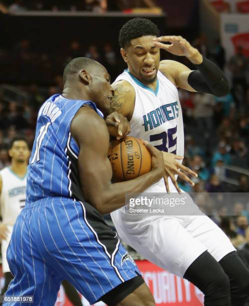 Bismack Biyombo of the Orlando Magic battles for a loose ball against Christian Wood of the Charlotte Hornets during their game at Spectrum Center on...