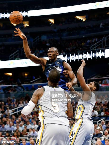 Bismack Biyombo of the Orlando Magic passes over JR Smith and Tristan Thompson of the Cleveland Cavaliers during the game at the Amway Center on...