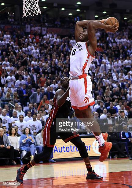 Bismack Biyombo of the Toronto Raptors dunks the ball as Luol Deng of the Miami Heat defends in the first half of Game Five of the Eastern Conference...