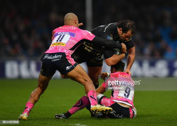 Bismark Du Plessis of Montpellier is tackled by Olly Woodburn and Nic White of Exeter Chiefs during the European Rugby Champions Cup match between...