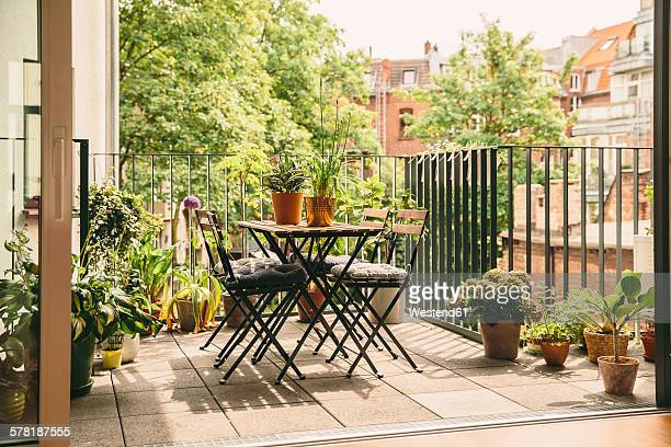 bistro chairs and table on balcony with view in the yard - バルコニー ストックフォトと画像